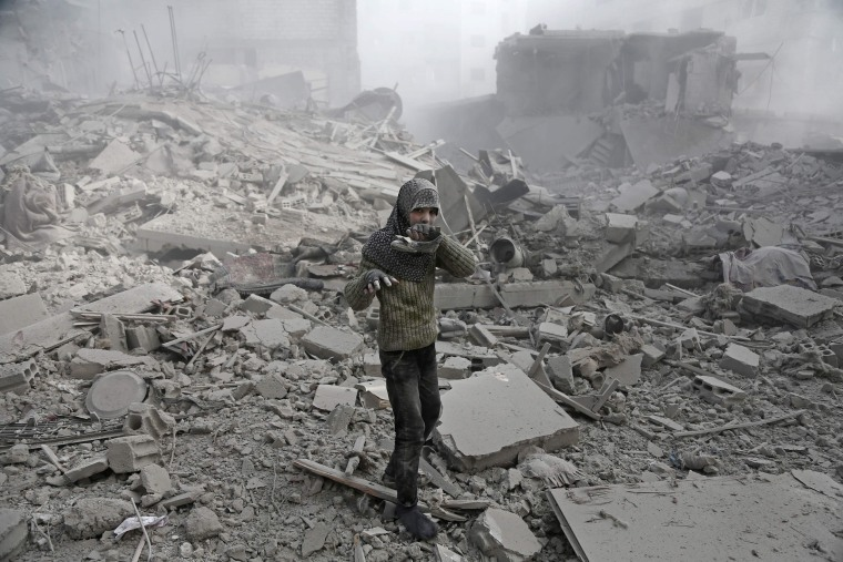 Image: A Syrian girl appears from the rubble holding her shoe