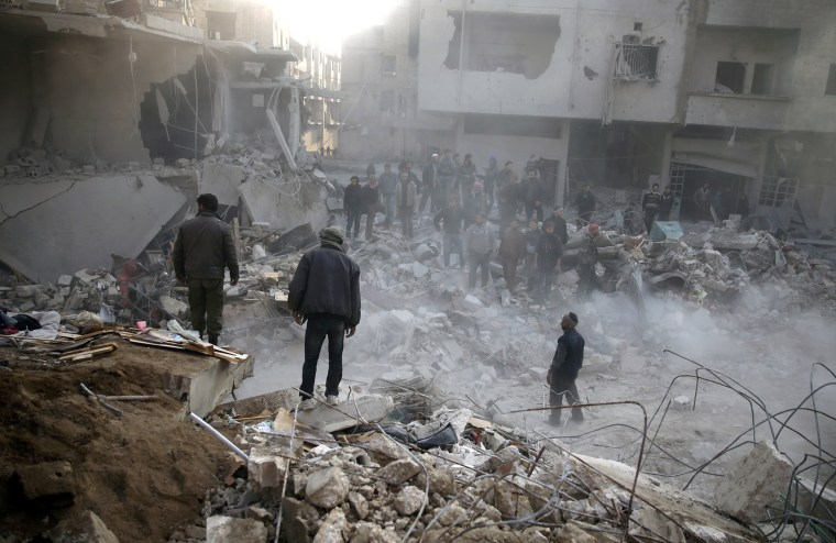 Image: People gather after airstrike in the besieged town of Hamoria, Damascus