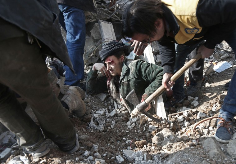 Image: Volunteers from the Syrian Civil Defence dig a man out of the rubble