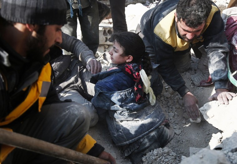 Image: Volunteers from the Syrian Civil Defense dig a girl out of the rubble