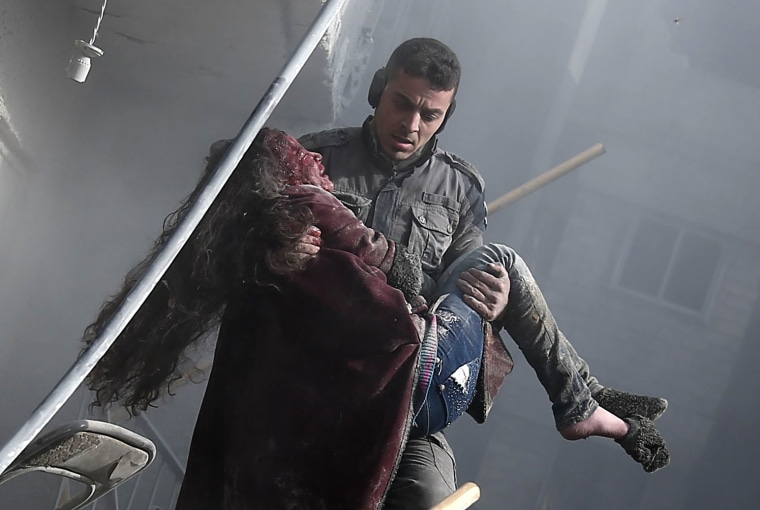 Image: A volunteer from the Syrian Civil Defense carries a wounded girl