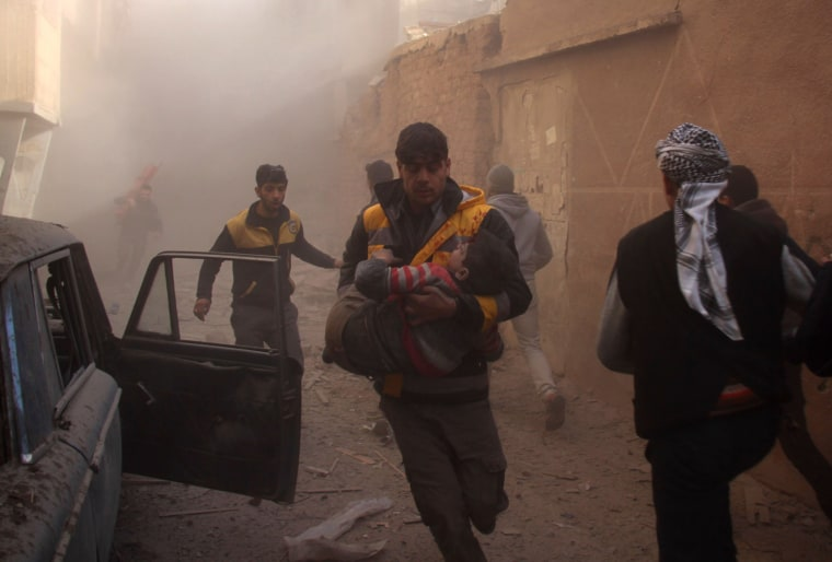Image: Members of the Syrian civil defence evacuate wounded people