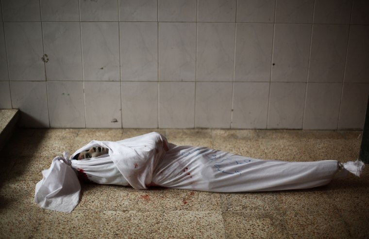 Image: The body of a child lies on the ground at a makeshift hospital