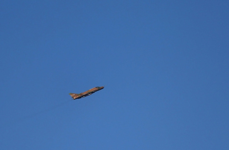 Image: A Syrian government plane flies over the rebel-held besieged town of Arbin