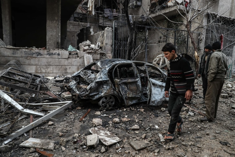 Image: A boy walks past a destroyed car after several air strikes on Hamoria