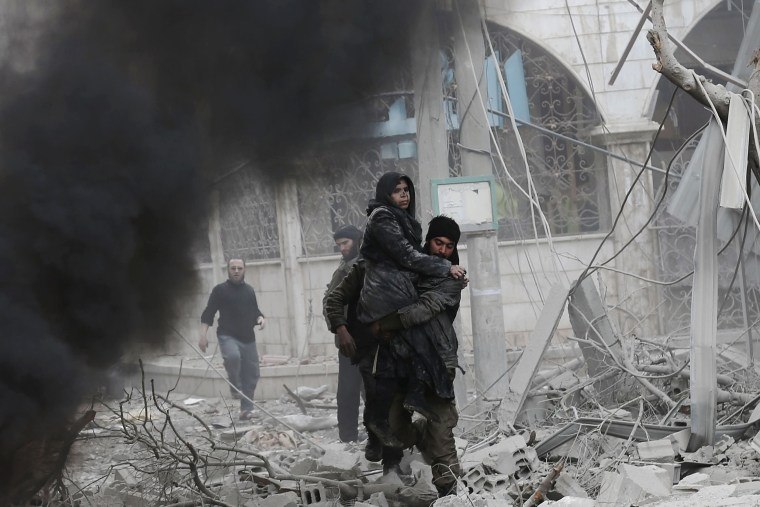 Image: A Syrian man carries an injured woman following air strikes
