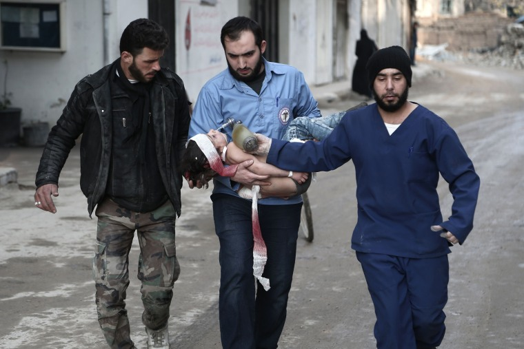 Image: Syrian civil defense volunteers carry a girl who was rescued from the rubble