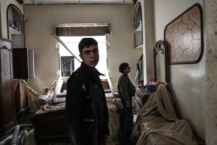 Image: Young boys walk inside a destroyed room in the aftermath of airstrikes on Mesraba