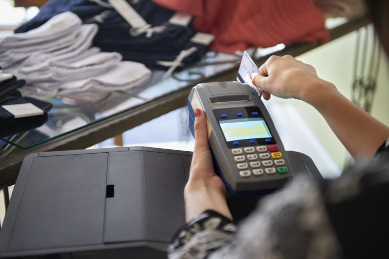 Image: Woman using credit card terminal in clothing shop