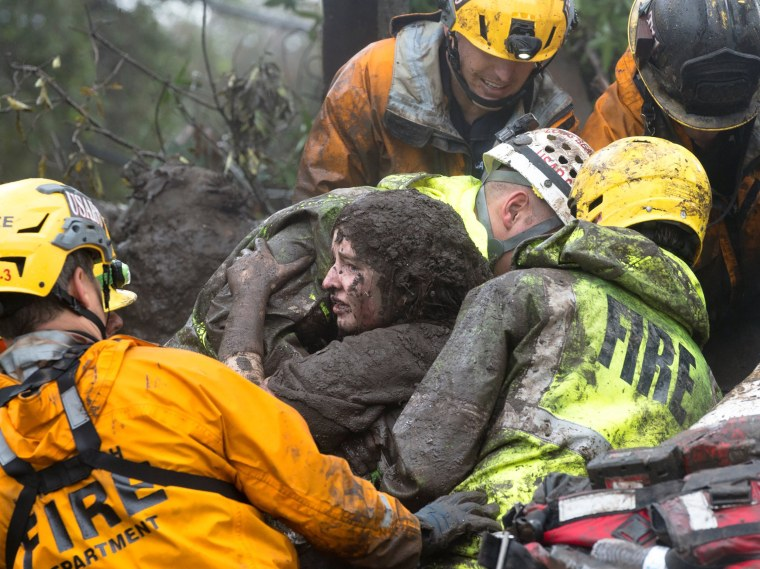 Image: Emergency personnel carry a woman rescued from a collapsed house after a mudslide in Montecito