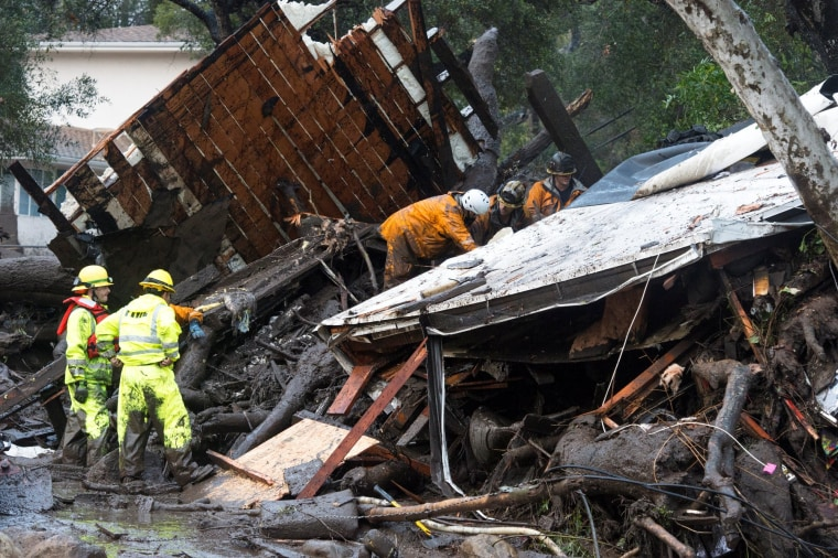 Image: Emergency personnel prepare to rescue a trapped woman inside a collapsed house in Montecito