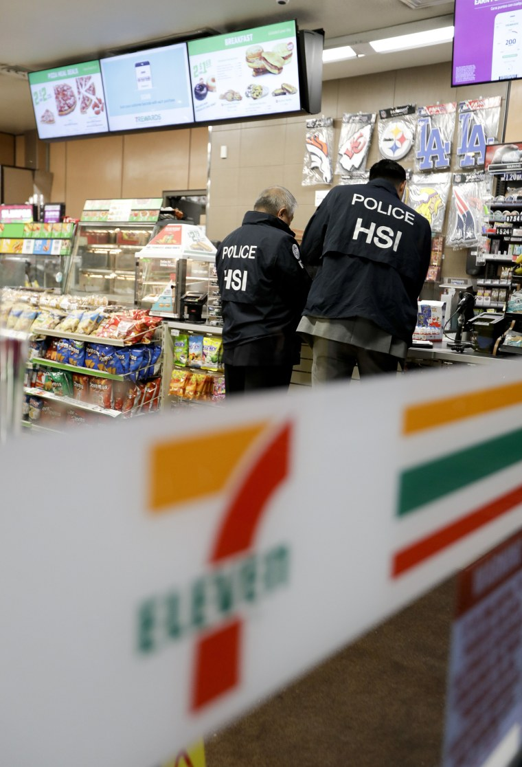 Image: U.S. Immigration and Customs Enforcement agents serve an employment audit notice at a 7-Eleven