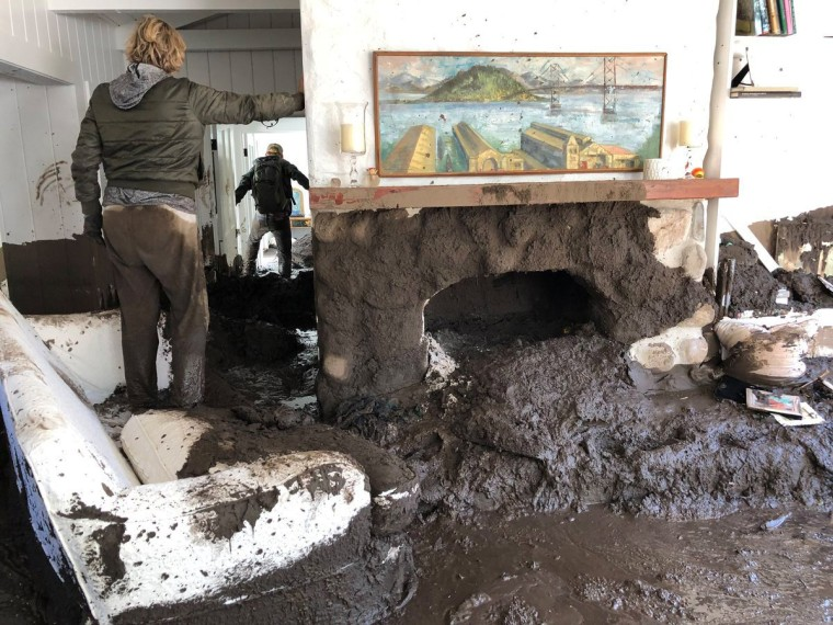 Image: Family members inspect the inside of a home covered in mud following the mudslides in Montecito