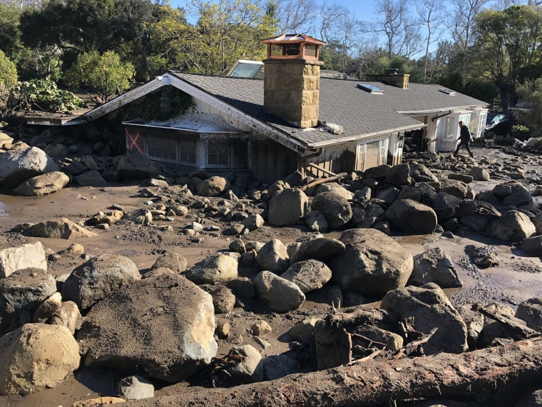 Image: Kerry Mann navigates the large boulders and mudflow that destroyed the home of her friend