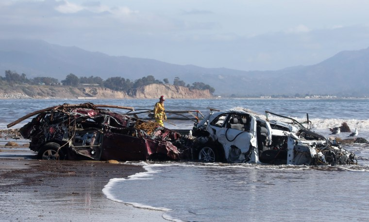 Image: Fremont City Firefighter Jordan Castro checks vehicles that had been washed into the Pacific Ocean