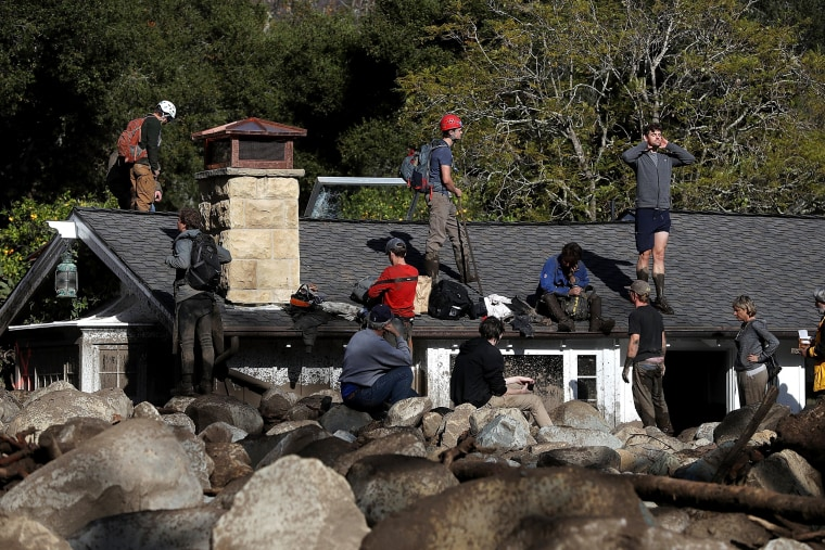 Image: Residents stand on a home that was destroyed by a mudslide