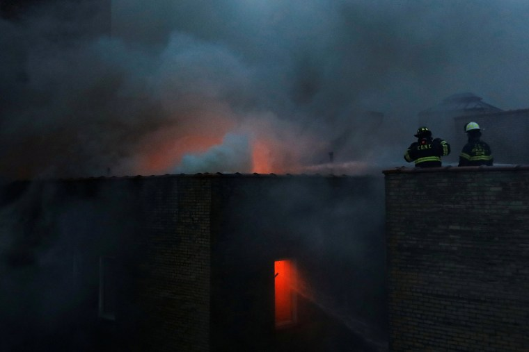 Image: Fire Department of New York (FDNY) firemen work on a six-alarm fire in Manhattan