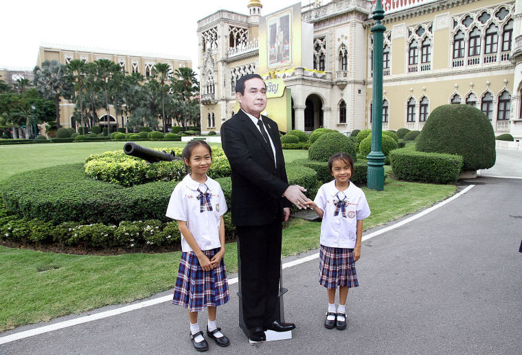 Image: Children pose next to a cardboard cut-out of Thailand's Prime Minster Prayuth Chan-ocha at the government house in Bangkok