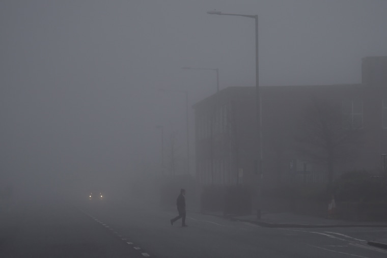 Image: A man walks through heavy fog in Belfast