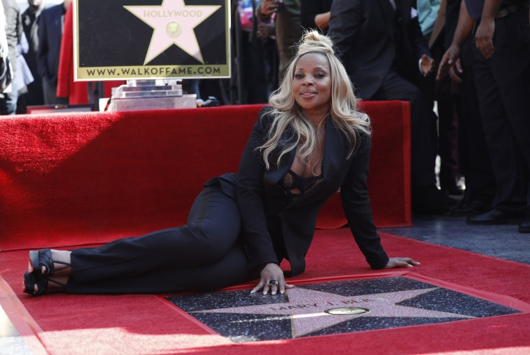 Image: Mary J. Blige sits next to her star on the Hollywood Walk of Fame