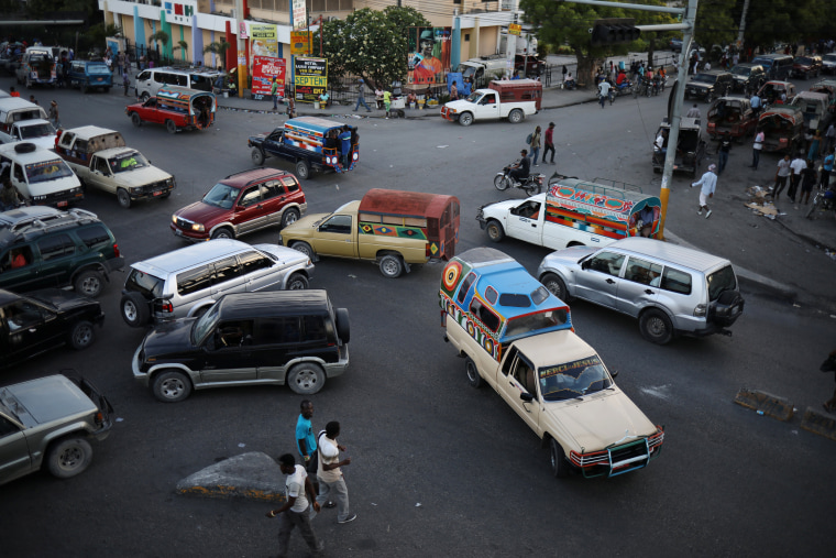 Image: Tap-tap trucks, collective transportation vehicles, and private cars drive in an intersection in Port-au-Prince