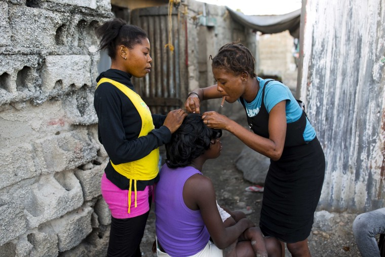 Image: A woman does her neighbor's hair in Cite Soleil