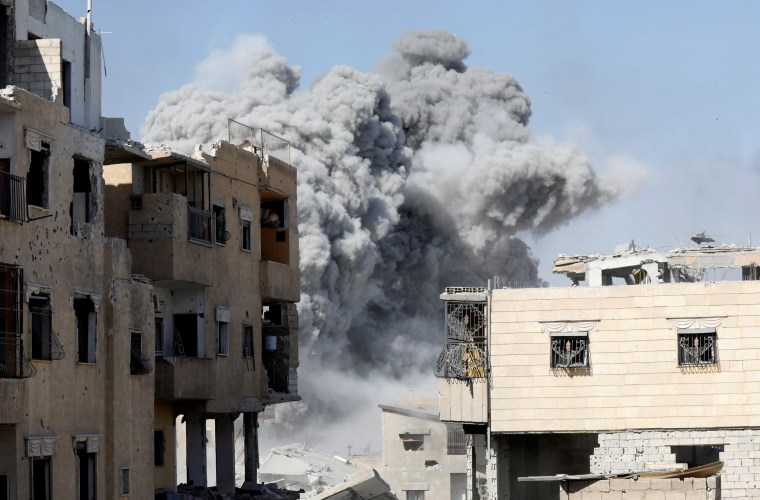 Image: Smoke rises at the positions of the Islamic State militants after an air strike by the coalition forces near the stadium in Raqqa