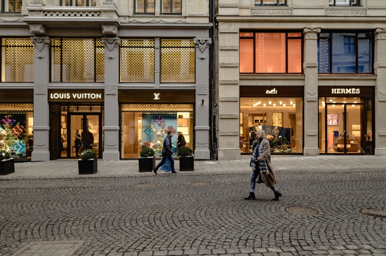 Image: People walk along a strip of designer storefronts in Oslo, Norway.
