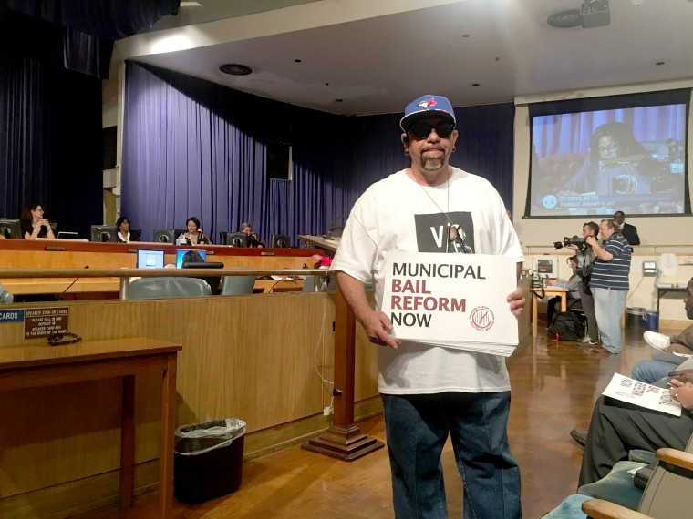 Image: A man poses with a sign at a a recent bail reform vote in New Orleans.