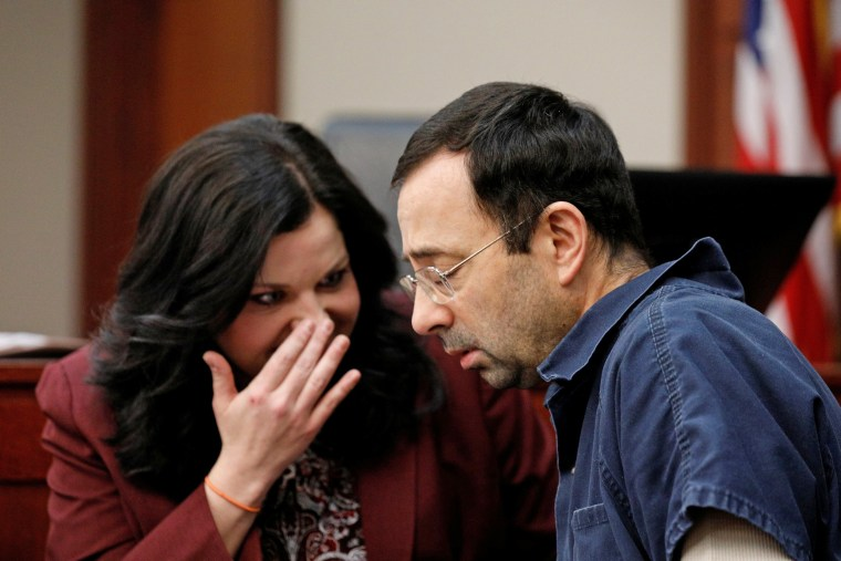 Image: Larry Nassar, a former team USA Gymnastics doctor, who pleaded guilty in November 2017 to sexual assault charges, speaks to his attorney Shannon Smith during his sentencing hearing in Lansing