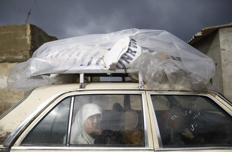 Image: A Palestinian woman rides in a car after collecting aid provided by the UN agency for Palestinian refugees, UNWRA, in Gaza City on Jan. 17, 2018.