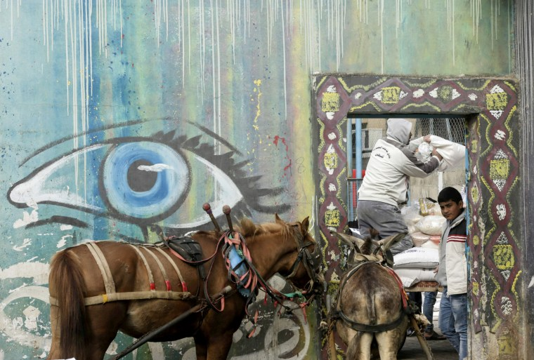 Image: A Palestinian man loads a horse-pulled cart with food donations inside a center of the UN agency for Palestinian refugees in the al-Nusirat refugee camp on Jan. 17.