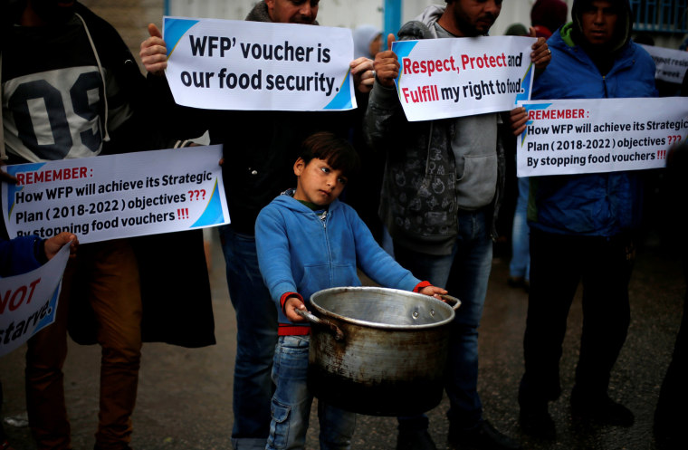 Image: A boy carries a cooking pot during a protest against the aid cut, outside of the United Nations' offices in Gaza City on Jan. 17.