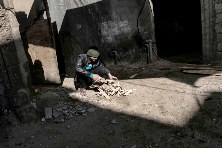 Image: A man chops wood in the Rafah refugee camp in the southern end of the Gaza Strip on Jan.17.