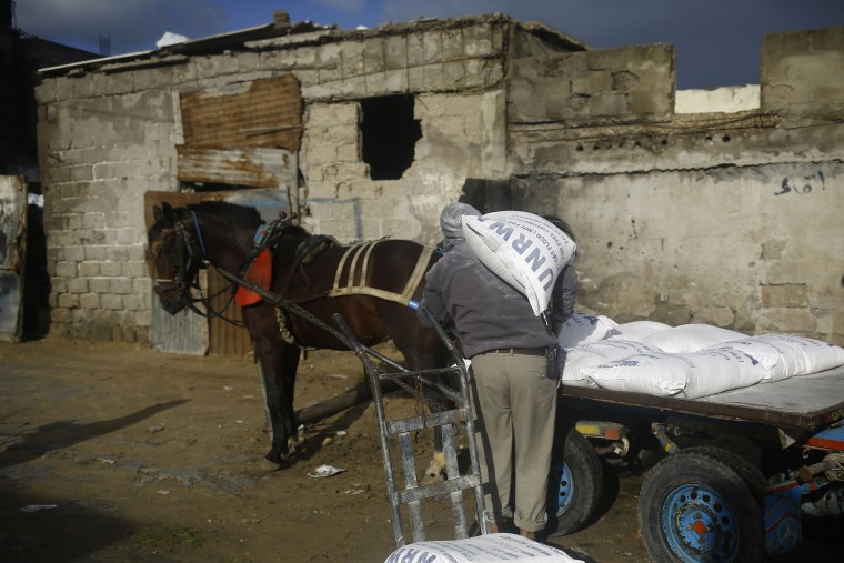 Image: A Palestinian man loads a horse-pulled cart with food donations outside of the UN food distribution on Jan. 15.