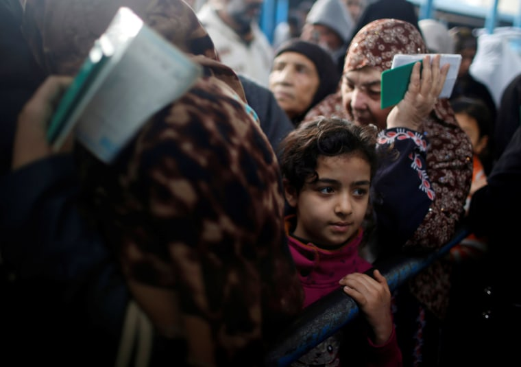 Image: Palestinian refugees wait to receive aid at a distribution center in the Al-Shati camp on Jan. 15.