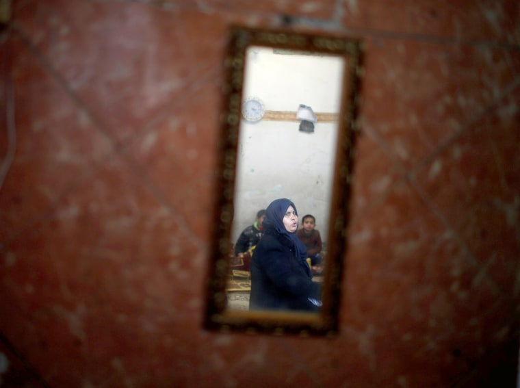 Image: A Palestinian woman is reflected in a mirror as she sits in her house in the Al-Shati camp on Jan. 17.