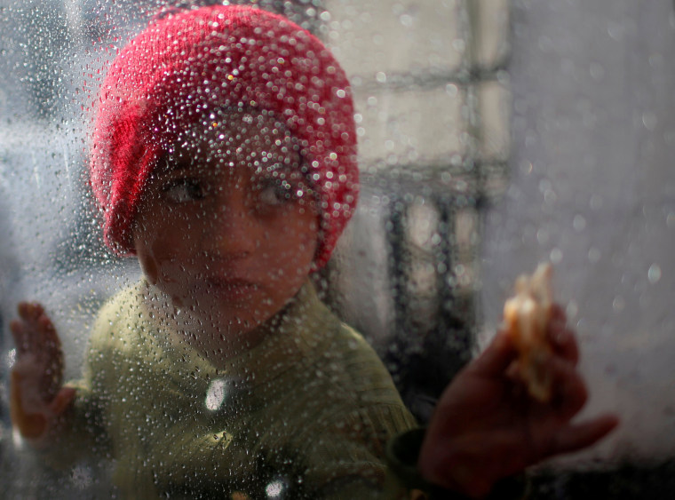 Image: A young girl looks through a plastic sheet as raindrops gather on its surface outside her family's house in the Al-Shati camp on Jan. 17.