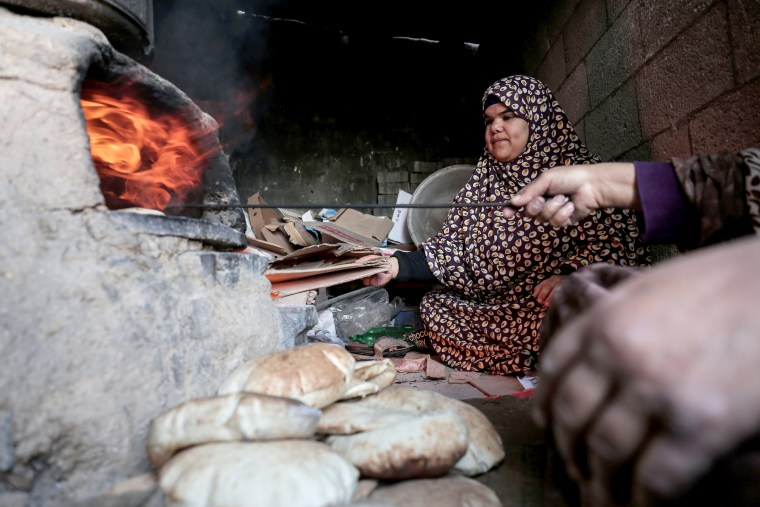 Image: Palestinian women bake bread at their house in the Rafah refugee camp on Jan. 17.