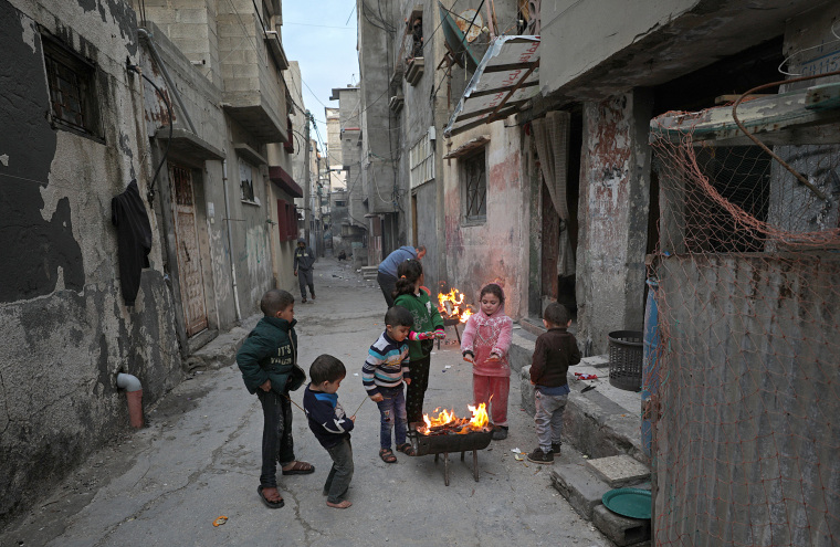 Image: Children warm themselves in the streets of al Shateaa refugee camp on, Jan. 17.
