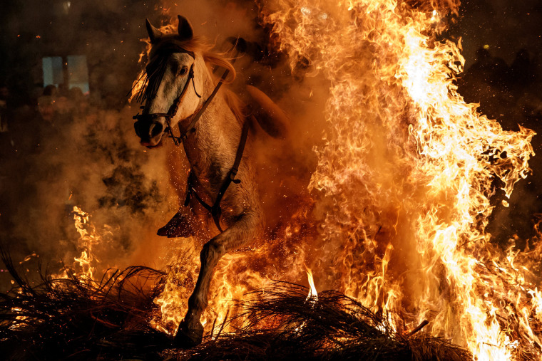 "Image: A man rides a horse through flames during the annual ""Luminarias"" celebration"