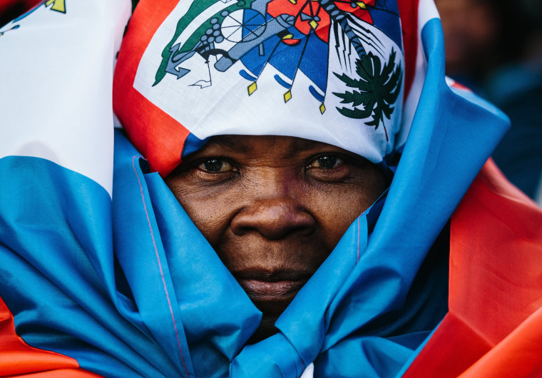 Image: A woman is wrapped in a Haitian flag at a rally against racism in New York