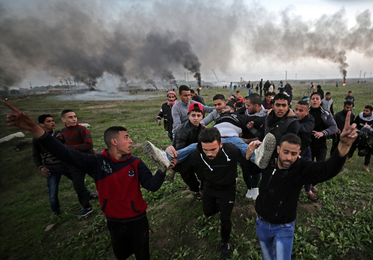 Image: Palestinian protesters carry a wounded man during clashes with Israeli troops