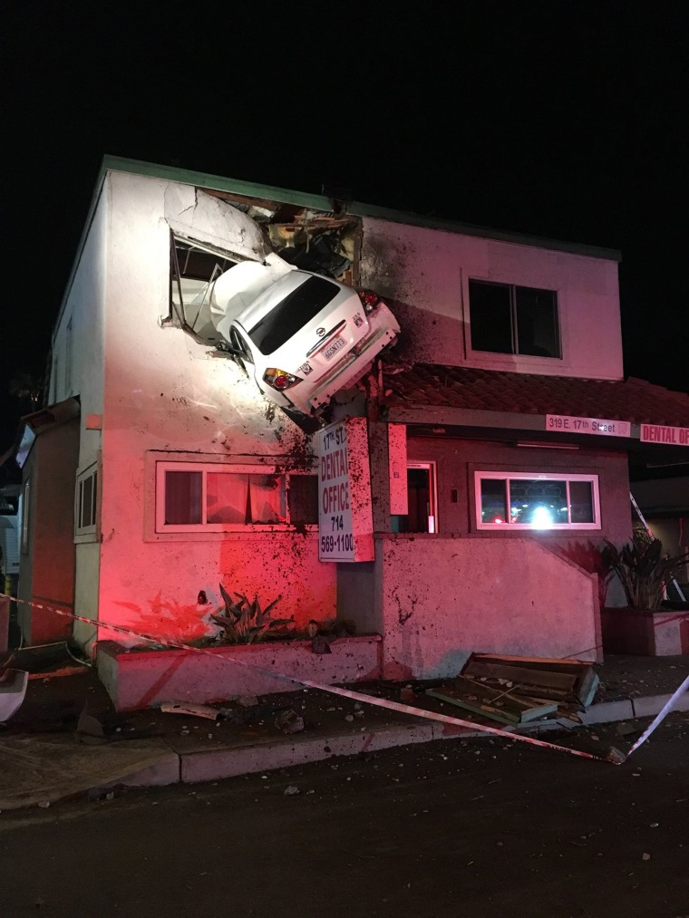 Image: A vehicle that crashed into a building hangs from a second story window in Santa Ana