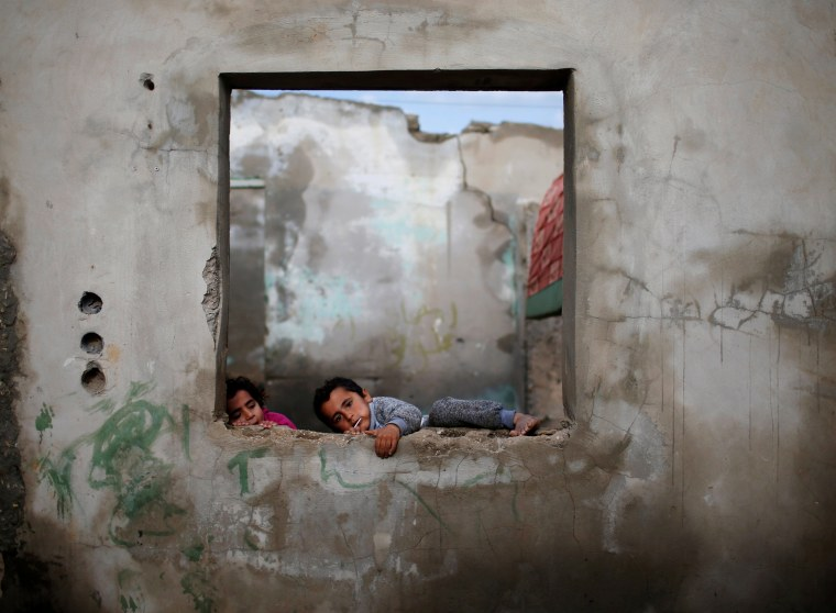 Image: Palestinian children play at their family's house in Al-Shati refugee camp in Gaza City