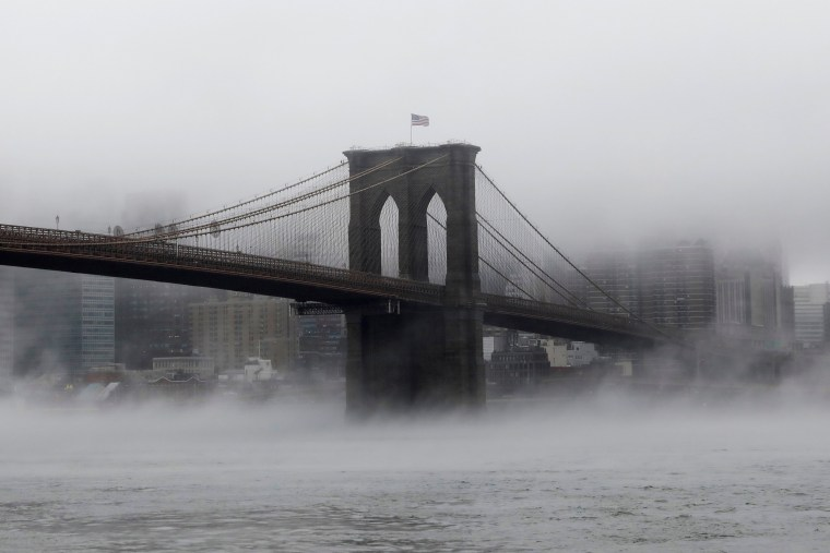Image: The Brooklyn Bridge is surrounded by fog that covers the Manhattan skyline