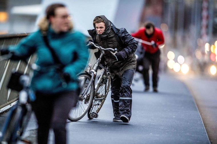 People walk with a bicycle through fierce winds in Rotterdam, The Netherlands, on January, 2018, during the second western storm of the year.
