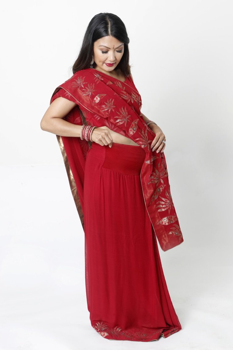 A red demi-panel maternity sari with pleats and petticoat stitched together and attached to a discreetly hidden stretchable demi (half) belly panel from Janam Maternity.