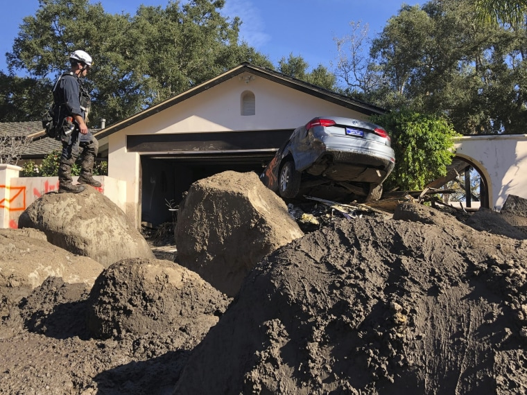 In this Jan. 13, 2018, file photo provided by the Santa Barbara County Fire Department, Capt. John Pepper, Fresno Fire Department, and Rescue Squad Leader RTF-5 searches homes off East Valley Road in Montecito, Calif.