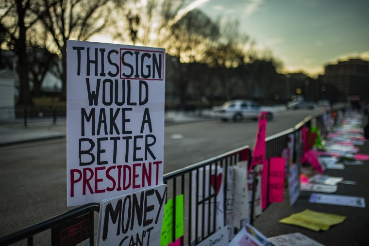 Image: Signs left by protesters lay on a fence in front of the White House.